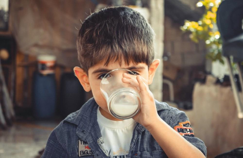 Niño bebiendo leche en vaso